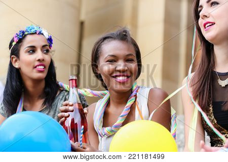 Four young women on hen night party drinking champagne on stairs