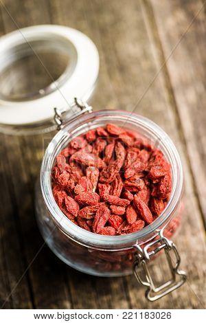 Dried goji berries in jar on old wooden table.