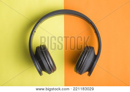 The headphones on double colorful background.