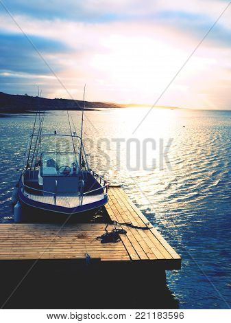 Fishing boat in bay port, sunset calm water. A motorboat for sport fishing tied to a wooden floating dock.
