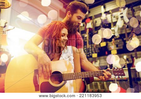 sale, people, musical instruments and entertainment concept - happy couple of musicians with guitar at music store over lights
