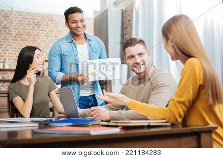 Interesting project. Cheerful smiling emotional student feeling excited while standing in front of his cheerful friends and waiting for them to discuss his interesting creative project