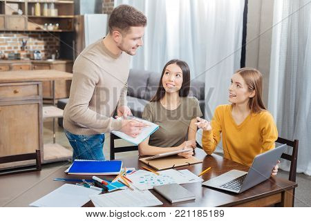 Looking interested. Smart enthusiastic responsible student standing with a big notebook in his hands while his cheerful beautiful friends looking at him and smiling