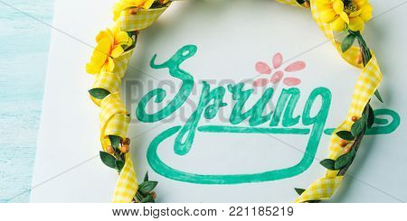 Spring word spelling by hand lettering and flower wreath girl head band. Flat lay season mood