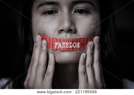 Young woman was wrapping her mount by adhesive tape,  Concept freedom of speech, censorship, freedom of press. International Human Right day.