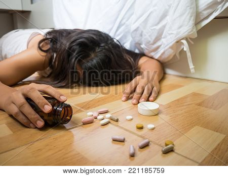 Woman lying on the floor after an overdose of pills at home.  Overdose and suicide concept.