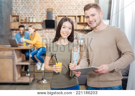 Smiling together. Smart young enthusiastic student standing with his clever cheerful colleague and holding a convenient modern tablet