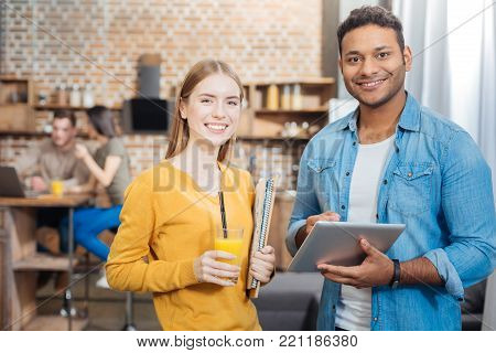 Useful gadget. Pleasant cheerful confident man looking glad while standing with a beautiful smiling student and holding a convenient modern gadget