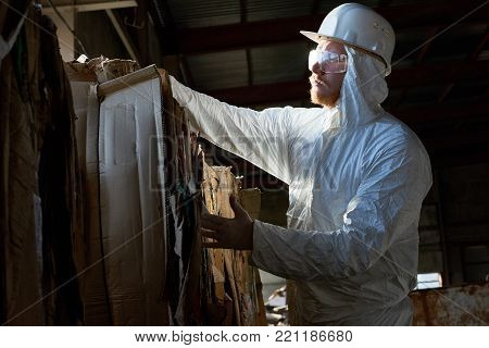 Side view portrait of factory worker wearing biohazard suit sorting reusable cardboard on waste processing, copy space