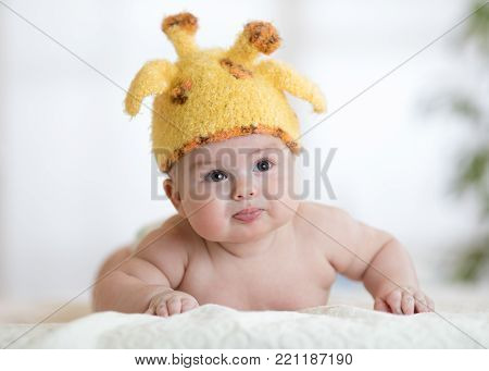 Newborn baby boy in funny giraffe hat lying on his belly in nursery