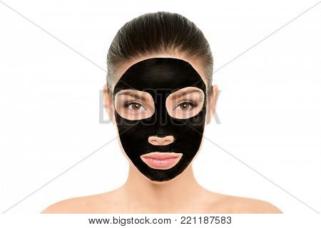 Black charcoal mask facial treatment Asian beauty woman. Wellness and spa purifying peel off mask face portrait, isolated on white background. Cleansing skin care to remove blackheads and clean pores.