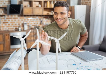 Cheerful engineer. Enthusiastic handsome young engineer having a productive day while sitting at the table and pointing to the tiny model of a windmill turbine