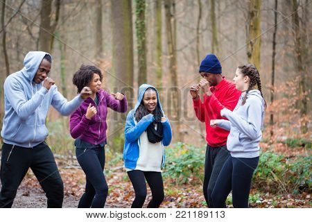 Determined young people warming up with boxing moves before workout session outdoors