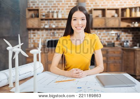 Diligent worker. Clever reliable enthusiastic engineer feeling happy while being at work and sitting at the table covered with schemes and drawings