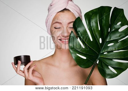happy smiling girl with a pink towel on her head applied a coffee scrub on her face, day spa