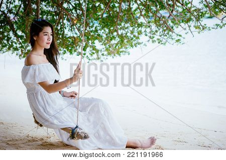 Asian girl wearing a long white dress sitting in the swing under trees at the beach on vacation weekend. Single lady sitting at the beach by alone. Girl with white dress on the beach.