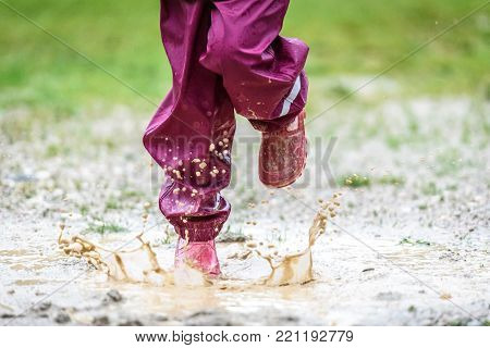 Children in rubber boots and rain clothes jumping in puddle. Water is splashing from girls feet as she is jumping and playing in the rain. Protective rubber pants and jacket for playing in the mud.