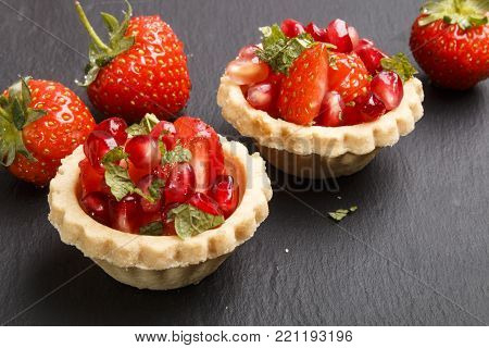 tartlets filled with strawberry, pomegranate seed and mint on slate