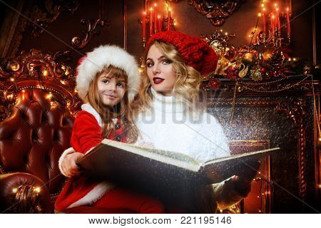 Pretty mother and daughter reading a book in luxury apartments decorated for Christmas. Merry Christmas and Happy New Year.
