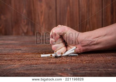 Man Breaks A Cigarette In His Hand. Quitting Smoking. Concept.