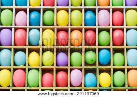 entertainment, party, amusement concept. there is a colorful background of popular attraction and contest with lots of balloons on the shelves in form of squares