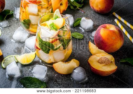 Summer refreshment drinks. Peach mojito with lime, peach and mint. With the ingredients on a dark stone table.