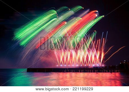 Beautiful, festive, colorful fireworks over the water with reflection. extremely long photo exposure