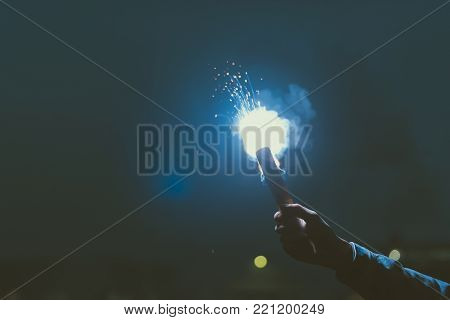 cropped view of male hand with smoke bomb at night