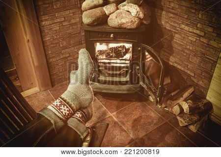 Feet in woollen socks by the Christmas fireplace. Man relaxes by warm fire with a cup of hot drink and warming up her feet in woollen socks. Close up on feet. Winter and Christmas holidays concept.