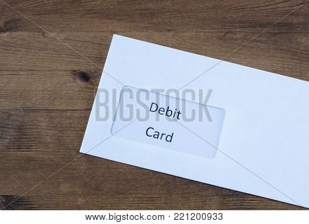 Letter on wooden table. Paper envelope with debit  card inside