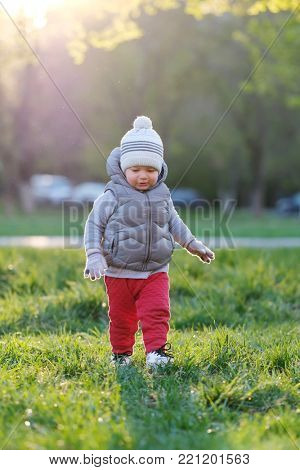 Portrait of toddler child in warm vest jacket outdoors. One year old baby boy wearing vest jacket at park meadow during sunset.