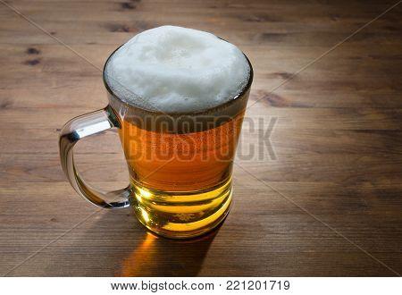 Glass of golden beer on wooden background. Selective focus
