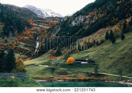 Rocky mountain with Schleierfall waterfall stream, autumn forest, meadow and house near Grossglockner Alpine Road in Alps, Austria
