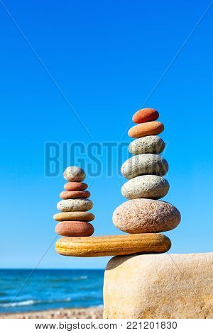 Two pyramids of colored balanced rocks on a background of blue sky and summer sea. Concept of balance, harmony and meditation