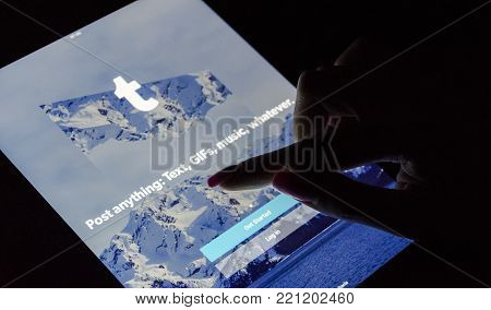 Sankt-Petersburg, Russia, December 21, 2017:  A woman's hand is touching screen on tablet iPad Pro at night with Internet service Tumblr on the screen. Tumblr is microblogging and social networking service.