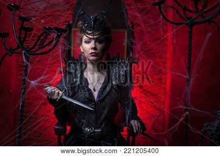 Woman in black dress sitting on a throne and holding a dagger.