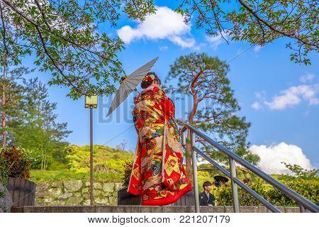 Kyoto, Japan - April 24, 2017: bottom view of back beautiful woman wear Japanese kimono and parasol standing in Kiyomizu-dera Temple. Unesco Heritage and popular landmark in Kyoto. Spring season.