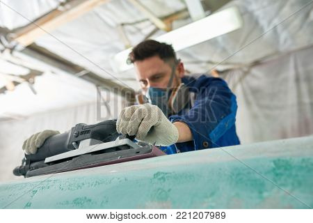 Portrait of worker wearing respirator repairing boat in yacht workshop using electric polishing tool, focus on foreground