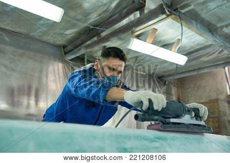 Portrait of mature modern man wearing respirator repairing boats in workshop using electric polishing tool, copy space