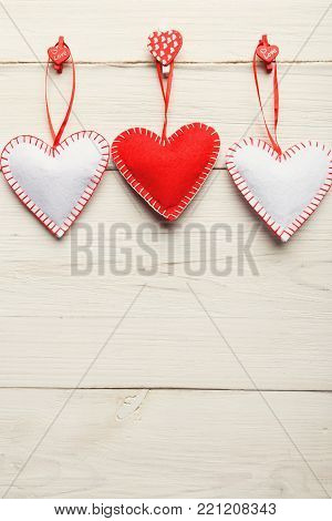 Valentine background with diy handmade sewed pillow hearts on red clothespins at rustic white wood planks. Happy lovers day card mockup, copy space