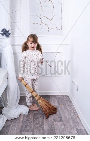 Little girl sweeping the floor standing by the bed in the bedroom