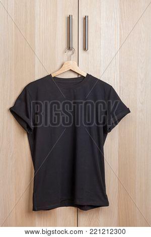Wrinkled black plain short sleeved cotton T-Shirt hanging on a wardrobe door handle