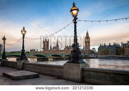 London cityscape with Dolphin lamp posts on the Queens Walk promenade between Lambeth Bridge and Tower Bridge in foreground and the Parliament, the Big Ben and the Westminster Bridge in background