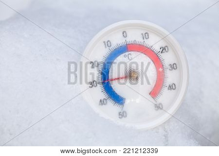 Frozen thermometer with celsius scale in snow showing extreme low sub-zero temperature minus thirty degree a cold winter weather concept