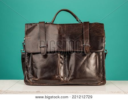 A vintage leather briefcase on a blue studio background
