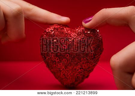 Two people holding a sparkling heart with fingertips
