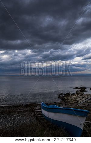landscape with a fishing boat on the waterfront with a dramatic sky. background in HDR, dramatic clouds and blue white boat.