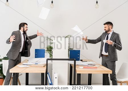 businessmen quarreling in office and throwing documents