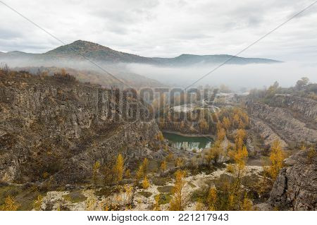 freedom, hiking, nature concept. light fog passed out between not high mountains, covered forest with turned yellow trees and small lake with water of beautiful emerald colour