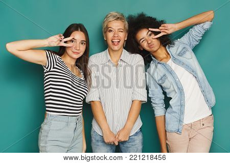 Happy female friends having fun at blue background. Three young women posing and laughing, slumber party, copy space